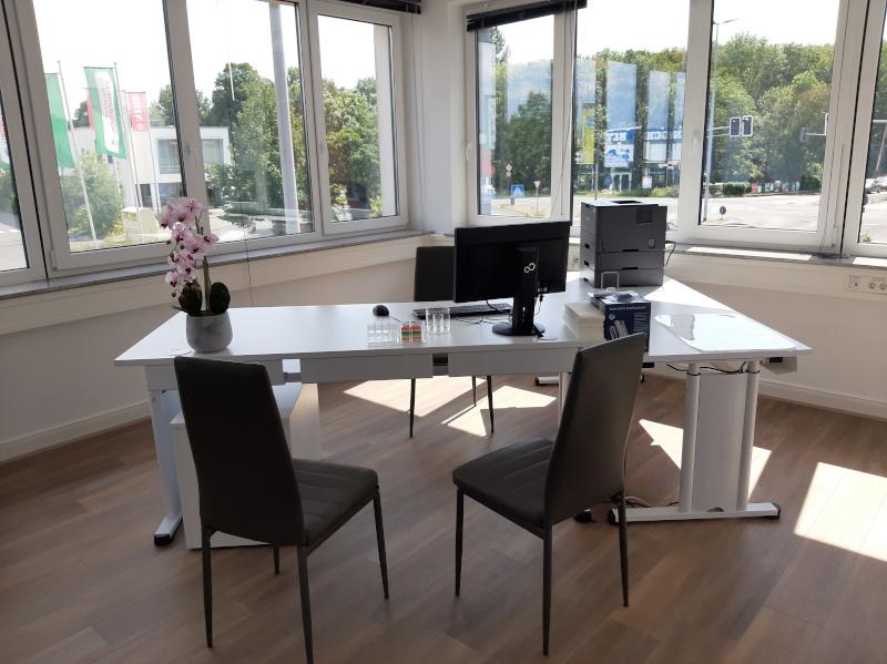 Weißer Tisch mit zwei Stühlen davor.